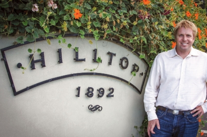 Erik Hendricks in front of the Hilltop 1892 sign
